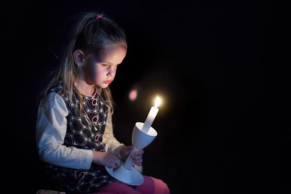 Kaitlyn holds a candle in front of her, lighting her face