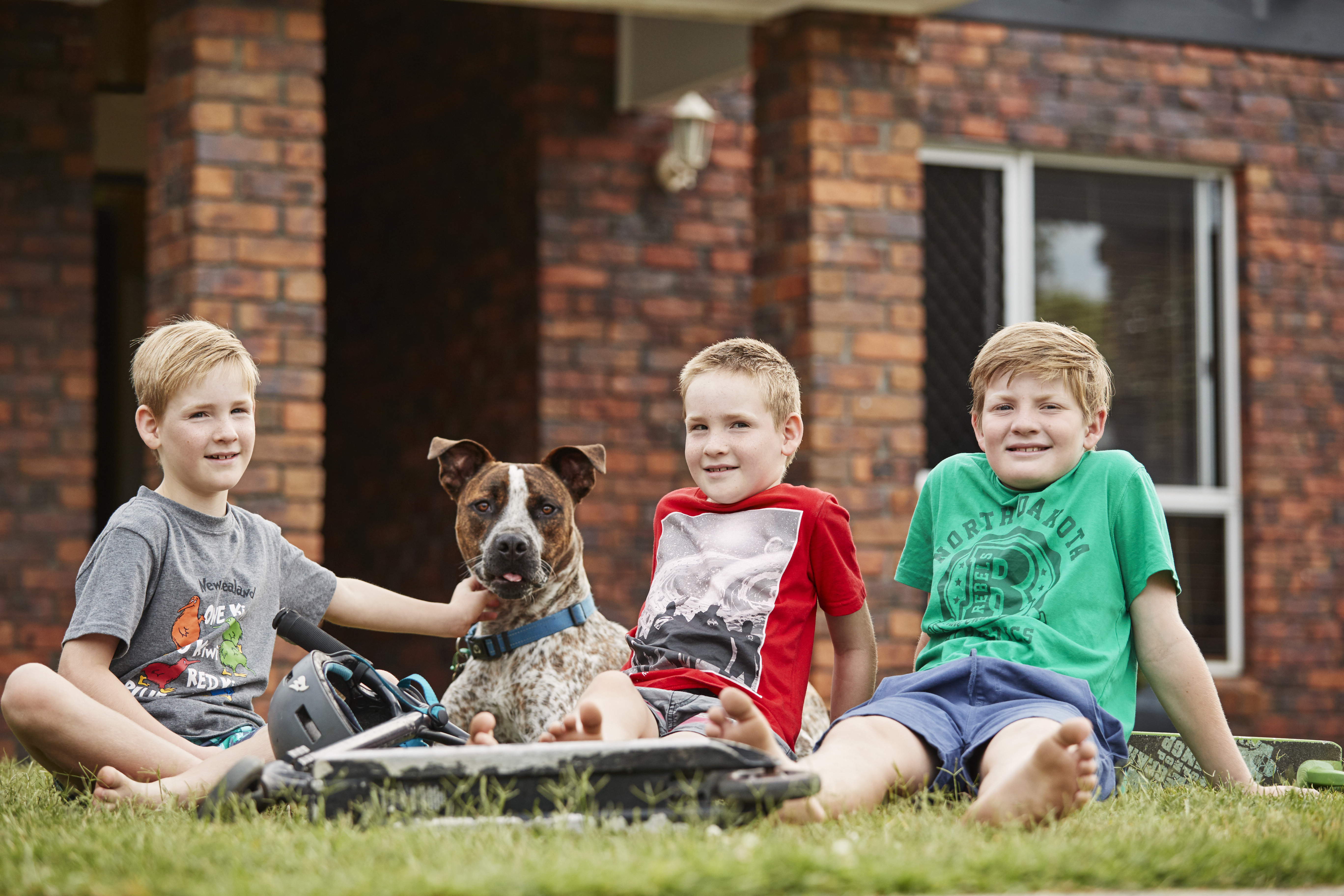 Three children sitting on the grass with their dog out the front of their home