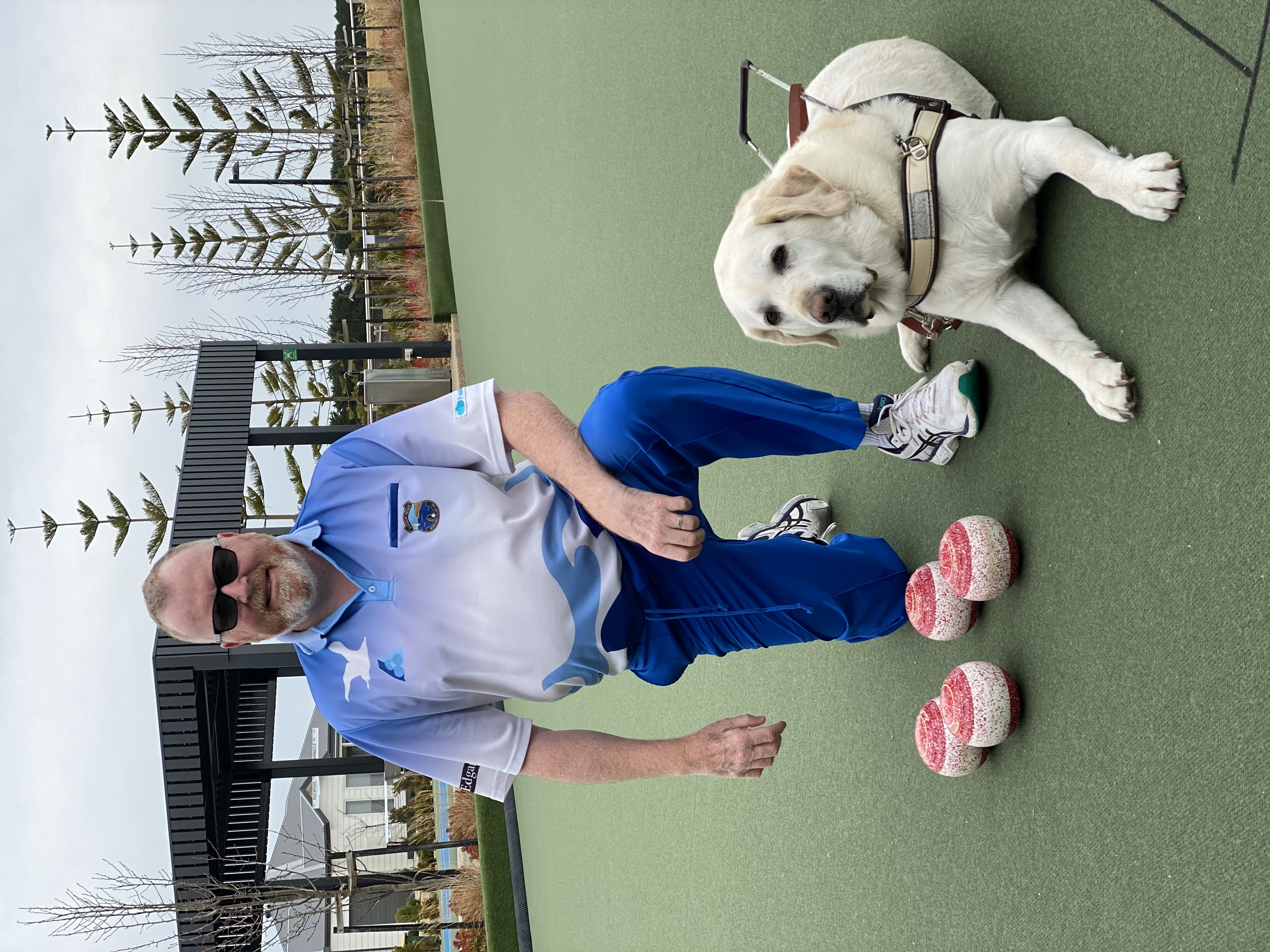 """ Greg Kennedy crouching with his dog guide Indrik on a Lawn Bowls court"""